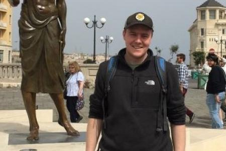 Cooper Hemphill in front of statue of Archimedes in Siracusa, Sicily